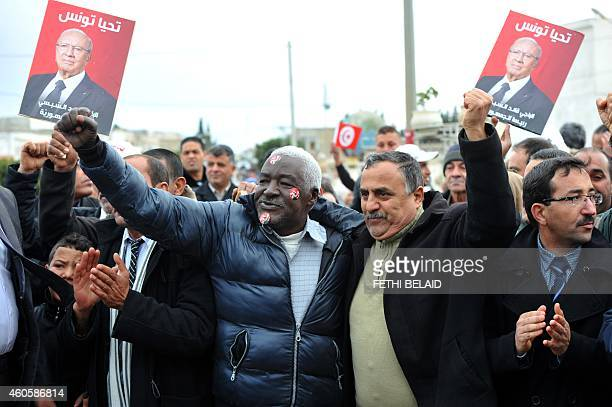 Supporters of Tunisian presidential candidate and former prime minister Beji Caid Essebsi hold up national flags and his portraits with the slogan...