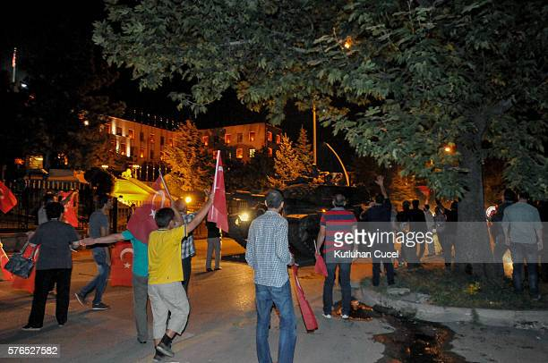 Supporters of Turkish President Recep Tayyip Erdogan react to a Turkish military tank in front of the Turkish Parliament July 15 2016 in Istanbul...