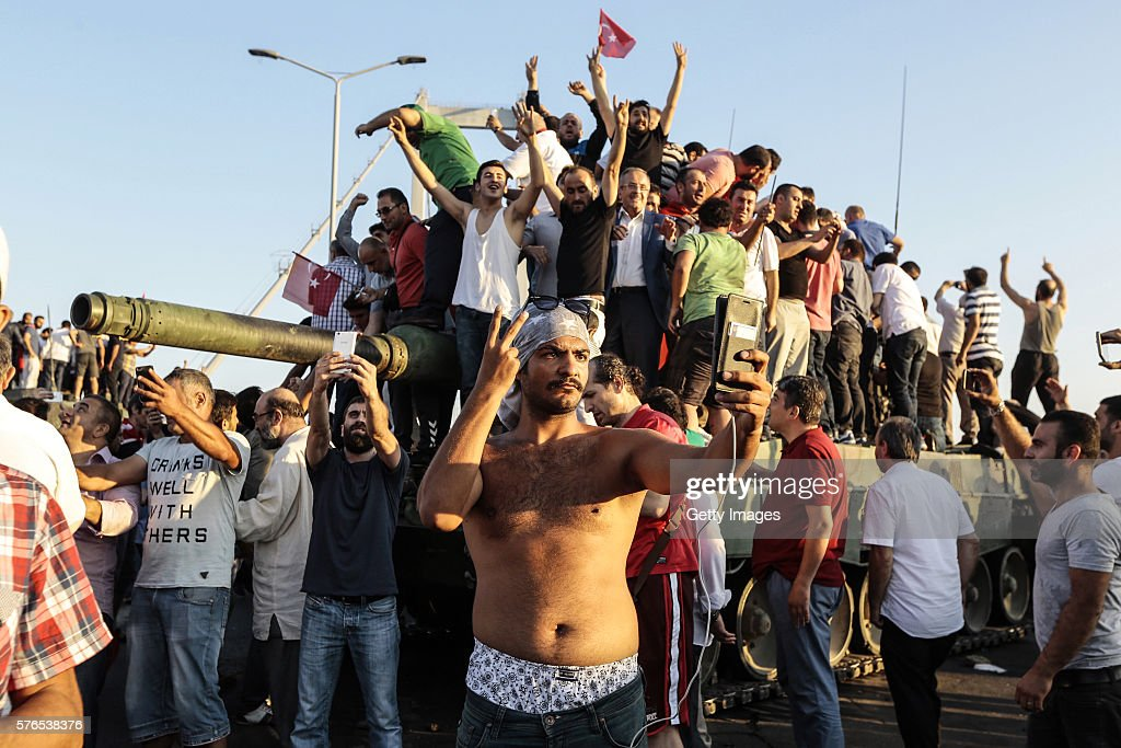 Supporters of Turkish President Recep Tayyip Erdogan wave flags as they capture anTurkish Army APC after soldiers involved in the coup surrendered on Bosphorus bridge on July 16, 2016 in Istanbul, Turkey. Istanbul's bridges across the Bosphorus, the strait separating the European and Asian sides of the city, have been closed to traffic. Turkish President Recep Tayyip Erdogan has denounced an army coup attempt, that has left atleast 90 dead 1154 injured in overnight clashes in Istanbul and Ankara.
