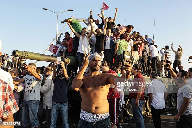 Supporters of Turkish President Recep Tayyip Erdogan wave flags as they capture anTurkish Army APC after soldiers involved in the coup surrendered on...