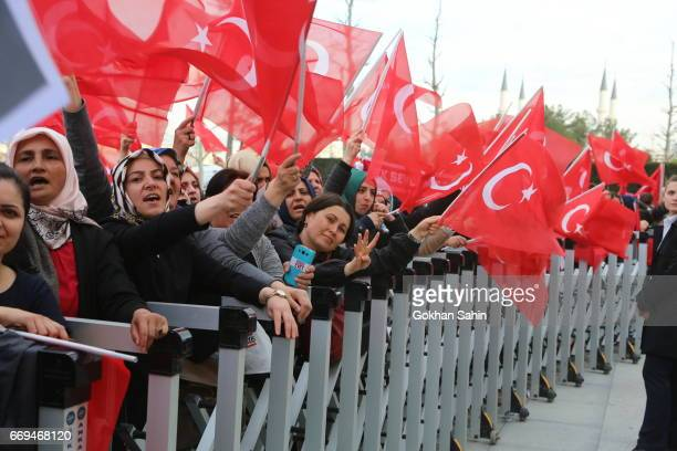 Supporters of Turkish President Tayyip Erdogan wave national flags as they wait for his arrival at the Presidential Palace on April 17 2017 in Ankara...