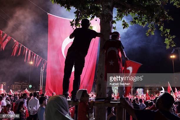 Supporters of Turkish President Tayyip Erdogan wave Turkish flags and light flares as they gather in Istanbul's central Taksim Square on July 19 2016...