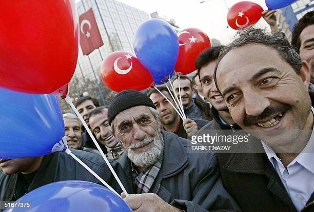 Supporters of Turkish Prime Minister Recep Tayyip Erdogan hold red and blue balloons symbolizing Europe and Turkey as they chant slogans during a...