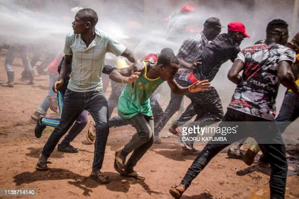 TOPSHOT Supporters of Ugandan musician turned politician Robert Kyagulanyi commonly known as Bobi Wine run away from a water cannon before the arrest...