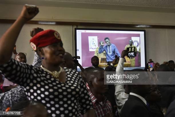 Supporters of Ugandan musician turned politician Robert Kyagulanyi aka Bobi Wine react as he gestures attending a court via video link in Kampala on...