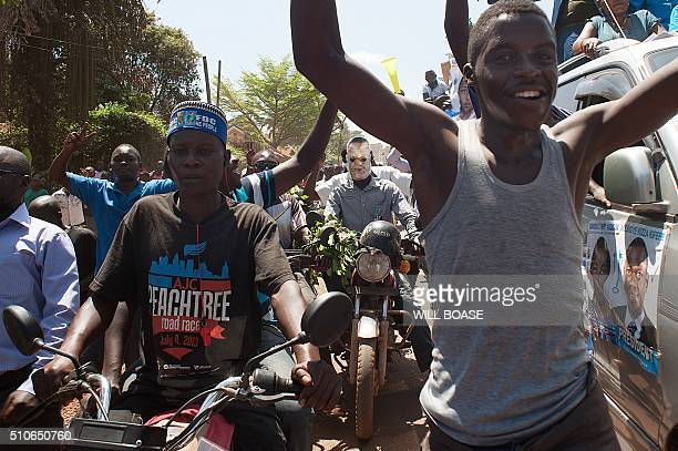 Supporters of Ugandan opposition leader and presidential candidate Kizza Besigye wearing campaign posters and hats run and ride on February 16 2016...