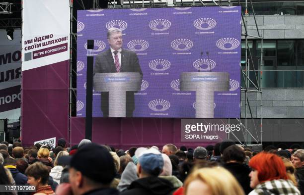 Supporters of Ukrainian President and presidential candidate Petro Poroshenko are seen watching Petro Poroshenko speaking on a screen and the empty...