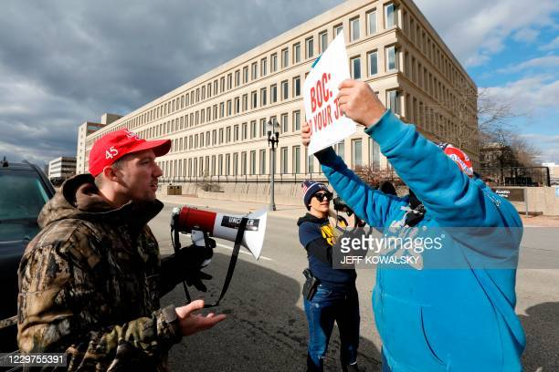 Supporters of US President Donald Trump and a supporter of US President-Elect Joe Biden argue in front of the Michigan State Capital as the Board of...