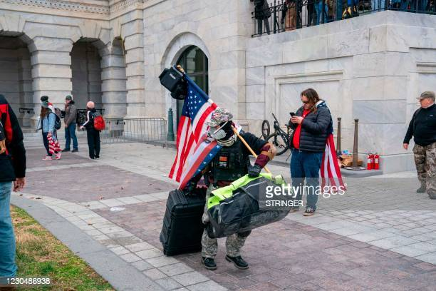 Supporters of US President Donald Trump carry looted items out of the US Capitol on January 6 in Washington, DC. - Donald Trump's supporters stormed...