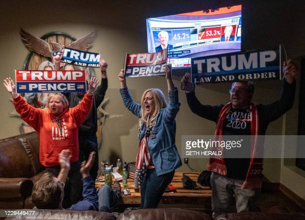 Supporters of US President Donald Trump celebrate as they watch Ohio being called for Donald Trump at a Republican watch party at Huron Vally Guns in...