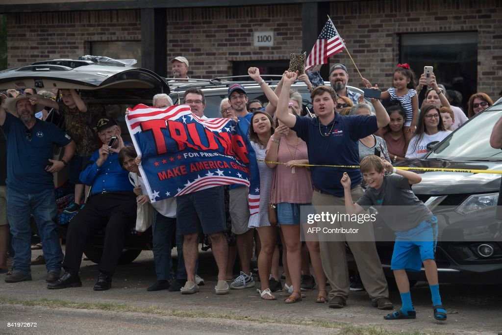 Supporters of US President Donald Trump cheer as he arrives in Lake Charles, Louisiana, on September 2, 2017. Trump is touring areas affected by Hurricane Harvey. /
