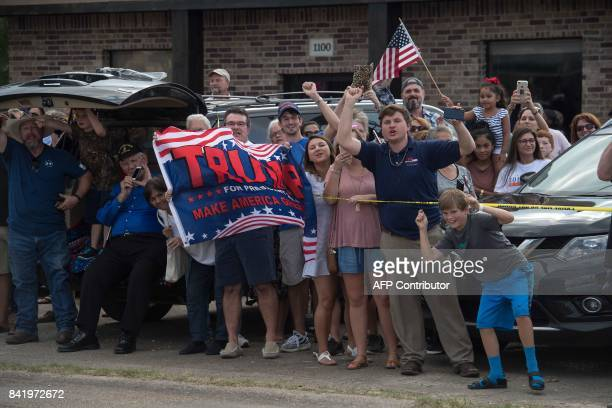 Supporters of US President Donald Trump cheer as he arrives in Lake Charles Louisiana on September 2 2017 Trump is touring areas affected by...