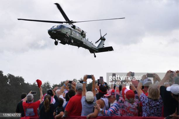 Supporters of US President Donald Trump cheer as Marine One lands for a campaign rally at The Villages Polo Club in The Villages, Florida on October...