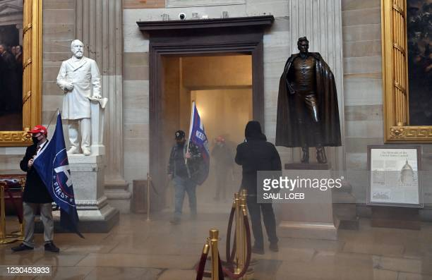 Supporters of US President Donald Trump enter the US Capitol's Rotunda as reported tear gas smoke fills a corridor on January 6 in Washington, DC. -...
