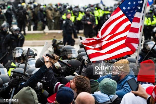 Supporters of US President Donald Trump fight with riot police outside the Capitol building on January 6, 2021 in Washington, DC. - Donald Trump's...