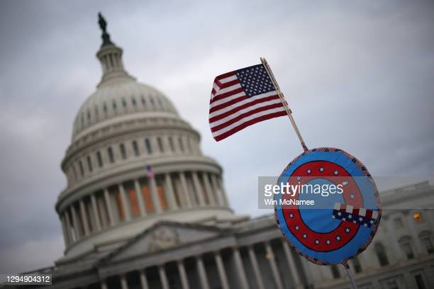 Supporters of U.S. President Donald Trump fly a U.S. Flag with a symbol from the group QAnon as they gather outside the U.S. Capitol January 06, 2021...