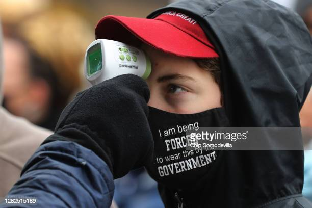 Supporters of U.S. President Donald Trump have their temperature taken as a precaution against the coronavirus before attending a campaign rally at...