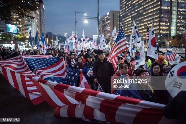 Supporters of US President Donald Trump hold a giant US flag as they wait for Trump's convoy to pass through the Gwanghwamun area of central Seoul on...