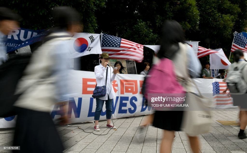 TOPSHOT - Supporters of US President Donald Trump hold a rally for the summit between Trump and North Korean leader Kim Jong Un in front of Japanese Prime Minister Shinzo Abe's official residence in Tokyo on June 12, 2018. - Donald Trump and Kim Jong Un became on June 12 the first sitting US and North Korean leaders to meet, shake hands and negotiate to end a decades-old nuclear stand-off.