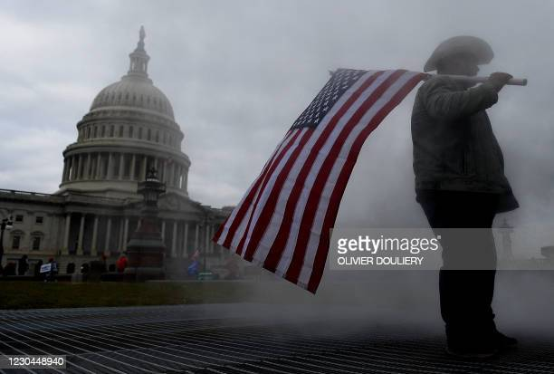 Supporters of US President Donald Trump hold a rally outside the US Capitol as they protest the upcoming electoral college certification of Joe Biden...