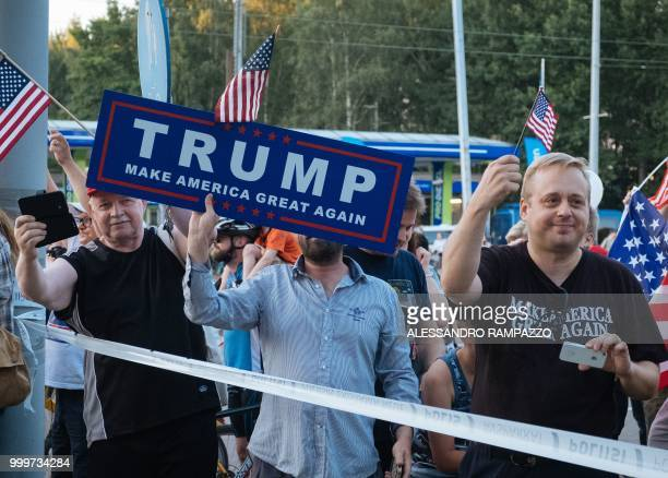 TOPSHOT Supporters of US President Donald Trump hold an US flag as the Presidential motorcade passes by in Helsinki Finland on July 15 on the eve of...