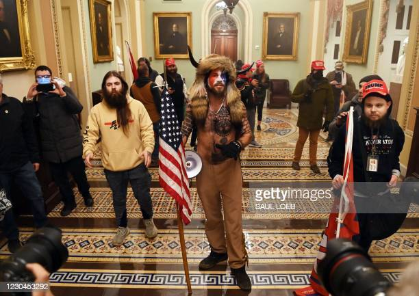 Supporters of US President Donald Trump, including Jake Angeli , a QAnon supporter known for his painted face and horned hat, enter the US Capitol on...