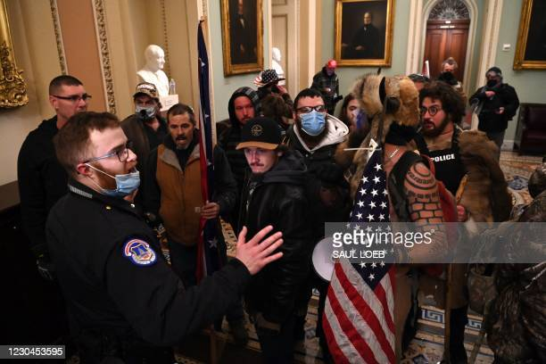 Supporters of US President Donald Trump, including Jake Angeli, a QAnon supporter known for his painted face and horned hat, protest in the US...