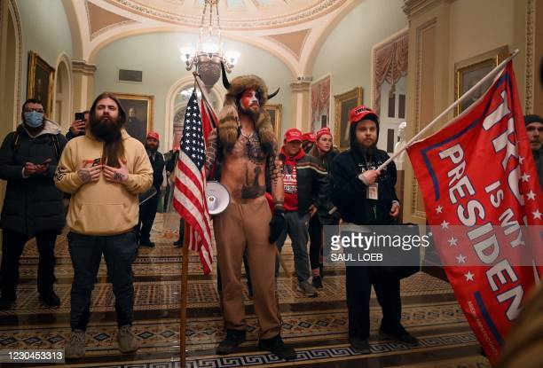 Supporters of US President Donald Trump, including member of the QAnon conspiracy group Jake Angeli, aka Yellowstone Wolf , enter the US Capitol on...