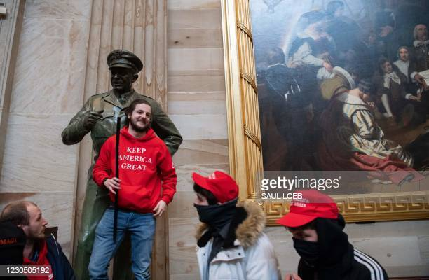 Supporters of US President Donald Trump pose with statues inside the Rotunda after breaching the US Capitol in Washington, DC, January 6, 2021. - The...