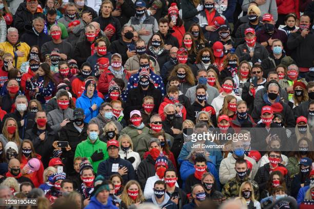Supporters of U.S. President Donald Trump say the Pledge of Allegiance before a campaign rally at North Coast Air aeronautical services at Erie...