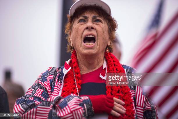 Supporters of US President Donald Trump sing the National Anthem as they rally for the president during his visit to see the controversial border...