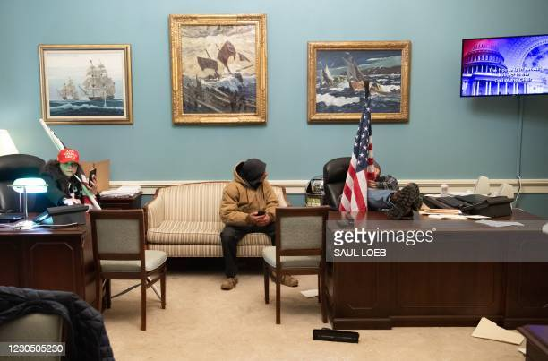 Supporters of US President Donald Trump sit at desks in the office suite of Speaker of the House Nancy Pelosi after breaching the US Capitol in...