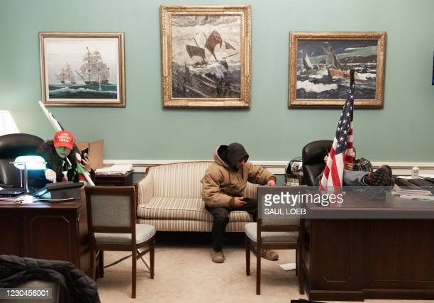 Supporters of US President Donald Trump sit inside the office of US Speaker of the House Nancy Pelosi as he protest inside the US Capitol in...