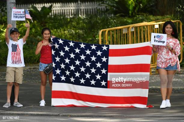 Supporters of US President Donald Trump stand on a sidewalk with placards and a US flag outside the Istana the official residence of the Singaporean...