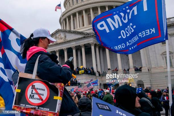 Supporters of US President Donald Trump stand on the US Capitol plaza on January 6 in Washington, DC. - Donald Trump's supporters stormed a session...