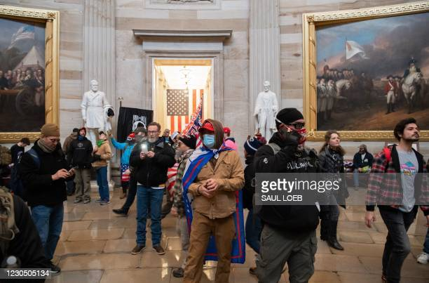 Supporters of US President Donald Trump walk around in the Rotunda after breaching the US Capitol in Washington, DC, January 6, 2021. - Demonstrators...