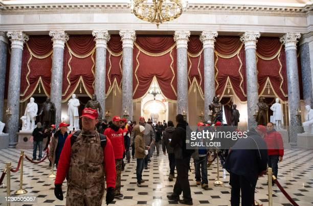 Supporters of US President Donald Trump walk through Statuary Hall after breaching the US Capitol in Washington, DC, January 6, 2021. - Demonstrators...