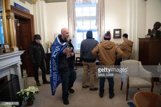 Supporters of US President Donald Trump walk through the office suite of Speaker of the House Nancy Pelosi after breaching the US Capitol in...