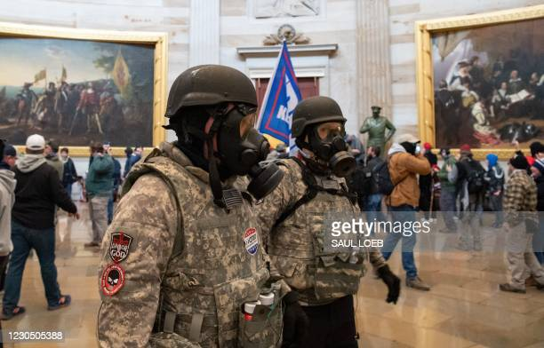 Supporters of US President Donald Trump wear gas masks and military-style apparel as they walk around inside the Rotunda after breaching the US...