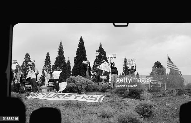 Supporters of US President George W Bush hold signs as Democratic presidential candiate US Senator John Kerry motorcade drives by October 22 2004 in...