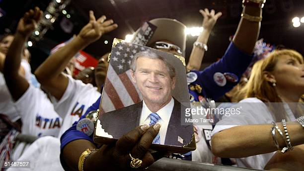 """Supporters of U.S. President George W. Bush hold up four fingers while chanting """"Four More Years"""" inside the Office Depot Center during a Florida..."""