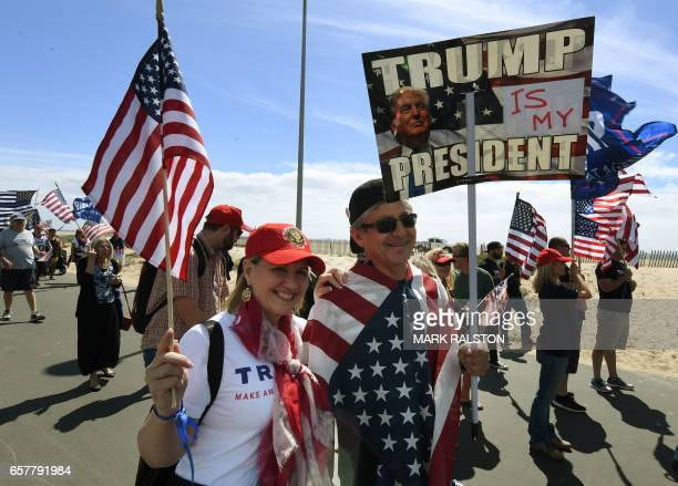 Supporters of US President Trump march during the Make America Great Again rally in Huntington Beach California on March 25 2017 / AFP PHOTO / Mark...