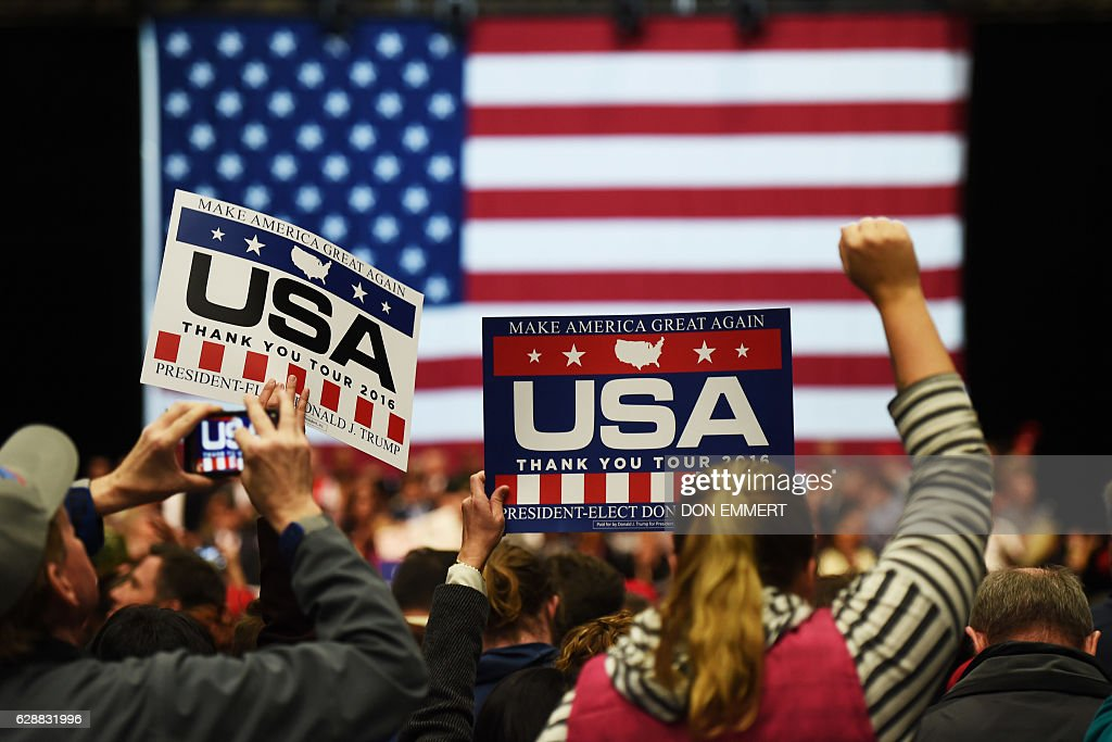 Supporters of US President-elect Donald Trump hold signs during the USA Thank You Tour December 9, 2016 in Grand Rapids, Michigan. / AFP / DON