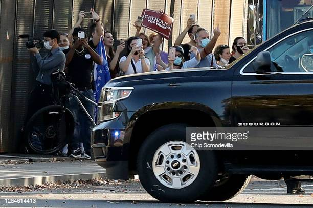 Supporters of U.S. President-elect Joe Biden and President Donald Trump cheer, hold signs, make photographs and gesture as Trump's motorcade returns...