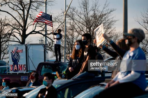 Supporters of US President-elect Joe Biden hold signs and wave flags as they listen to his speech outside Center Parc Stadium in Atlanta, Georgia, on...