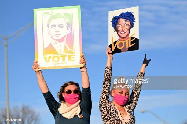 Supporters of US President-elect Joe Biden hold signs with Jon Ossoff and Stacy Abrams as they wait for his arrival outside Center Parc Stadium in...