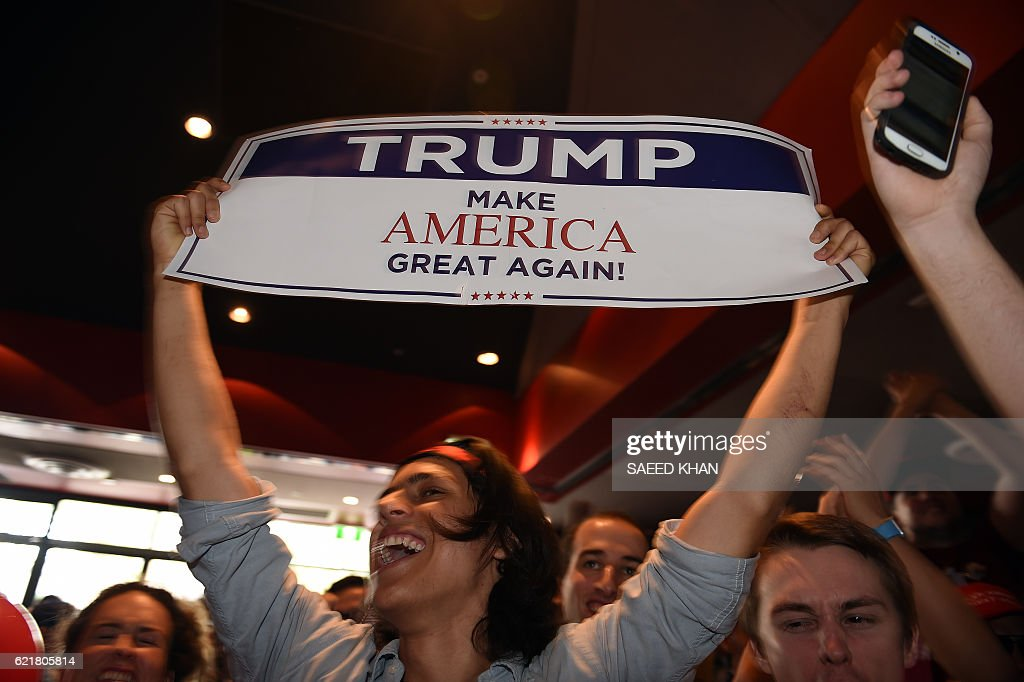 TOPSHOT - Supporters of US presidential canditate Donald Trump celebrates his seats at the United States Studies Center at the University of Sydney on November 9, 2016. Australian stocks climbed 0.80 percent at the open in anticipation of a victory for Hillary Clinton in the US presidential election. / AFP / SAEED