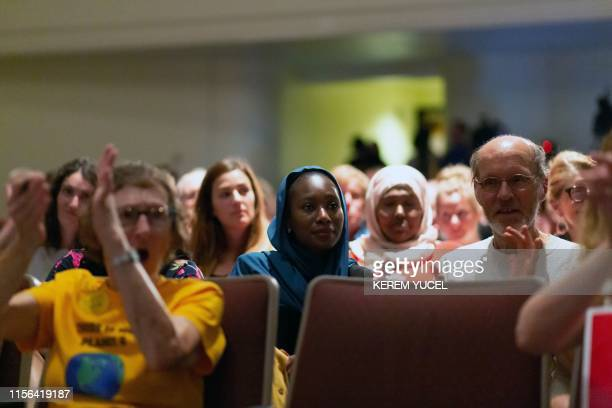 Supporters of US Representative Ilhan Omar applaud and listen as she speaks on stage during a town hall meeting at Sabathani Community in Minneapolis...