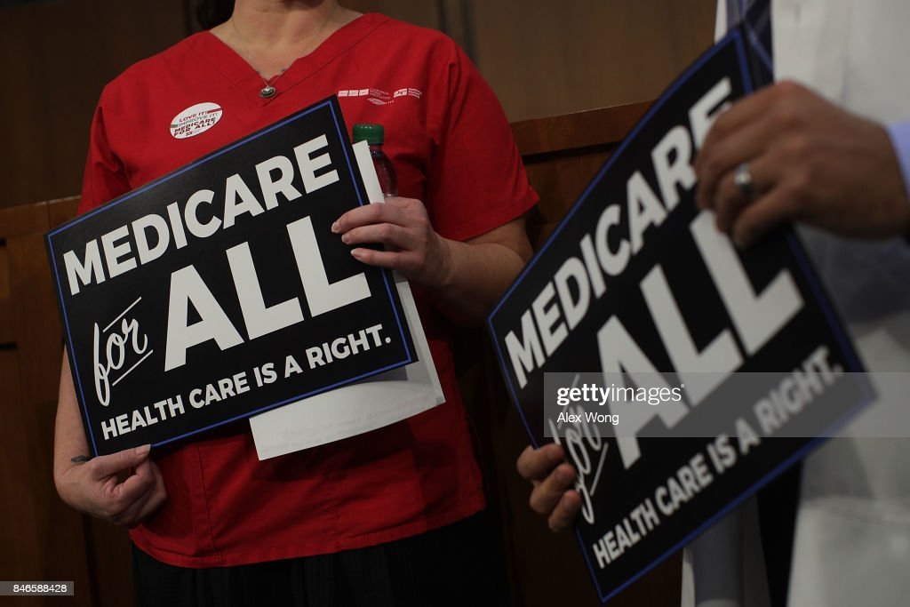 Supporters of U.S. Sen. Bernie Sanders (I-VT) hold signs during an event on health care September 13, 2017 on Capitol Hill in Washington, DC. Sen. Sanders held an event to introduce the Medicare for All Act of 2017.