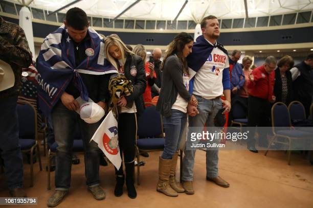 Supporters of US Sen Ted Cruz bow their heads in prayer before the start of a Get Out The Vote Bus Tour rally at the Amarillo Civic Center on October...